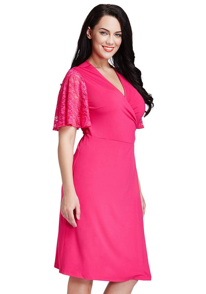 Right angle shot of model wearing hot pink plunge wrap-style dress