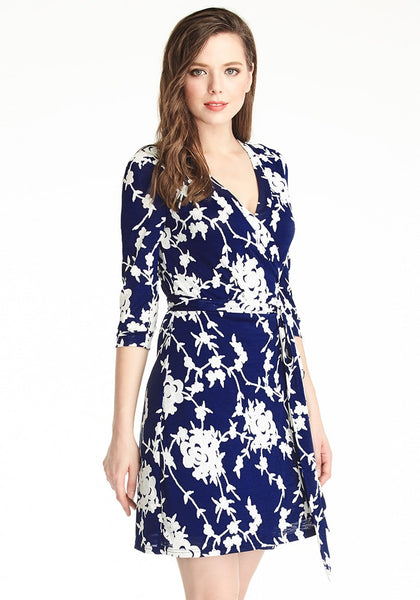 Right angle shot of woman in navy blue floral plunge wrap dress