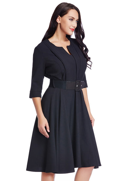 Right angle shot of woman in plus size black belted skater dress