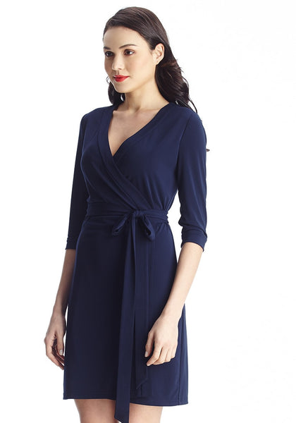 Right angled shot of brunette woman in navy plunge wrap-style belted dress