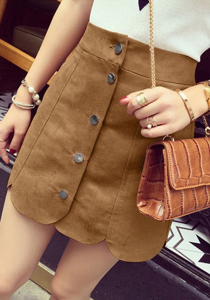 Right angled shot of girl's brown suede scallop hem miniskirt