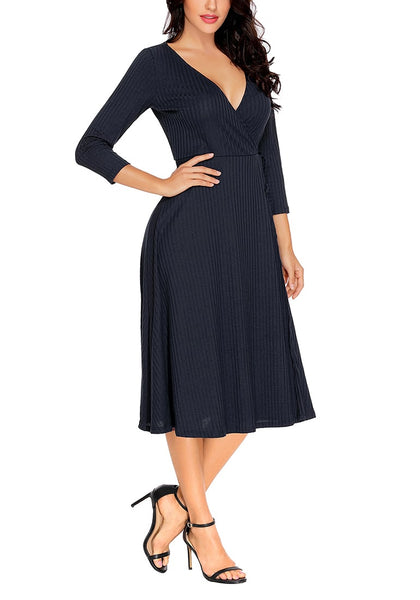 Right angled shot of model in navy bowknot textured faux wrap dress