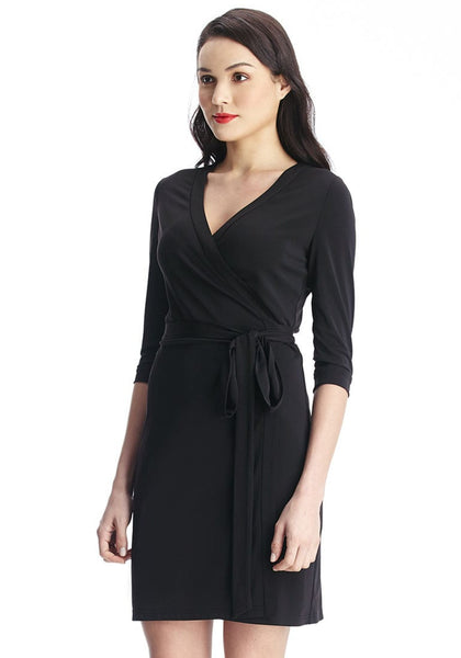 Right angled shot of woman in black plunge wrap-style belted dress