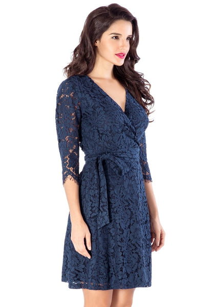 Right angled shot of woman wearing navy floral lace overlay wrap dress