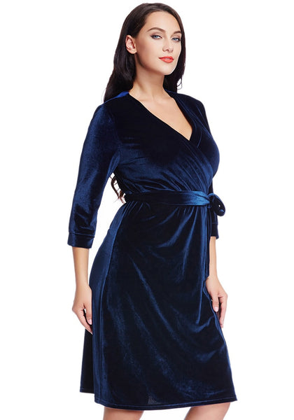 Right angled view of lady in plus size navy blue velvet wrap dress