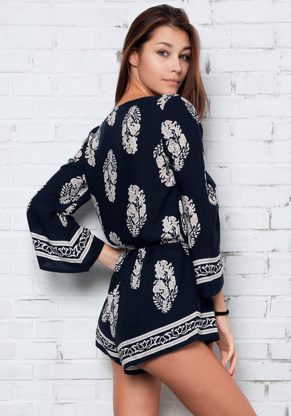Right side shot of model in foliage-print trumpet sleeve romper
