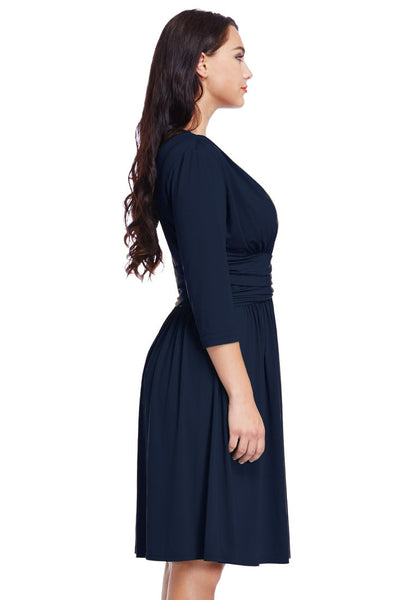 Right side angled view of model in plus size navy blue plunge tie-side wrap dress