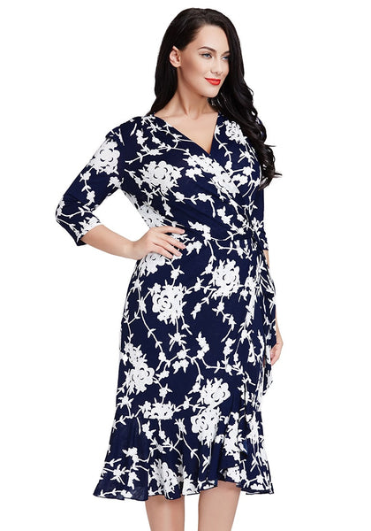 Right side shot of model in plus size blue floral ruffled wrap dress