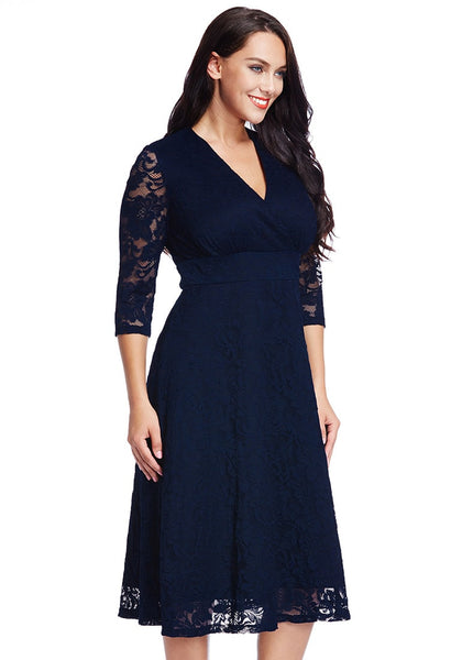 Right side shot of model in plus size navy lace surplice midi dress