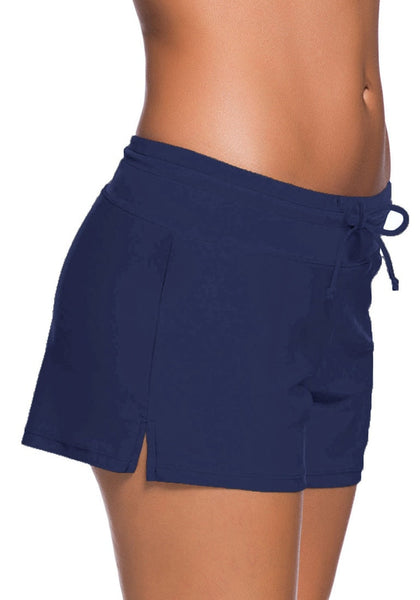 Right side shot of model in royal blue drawstring side-slit board shorts