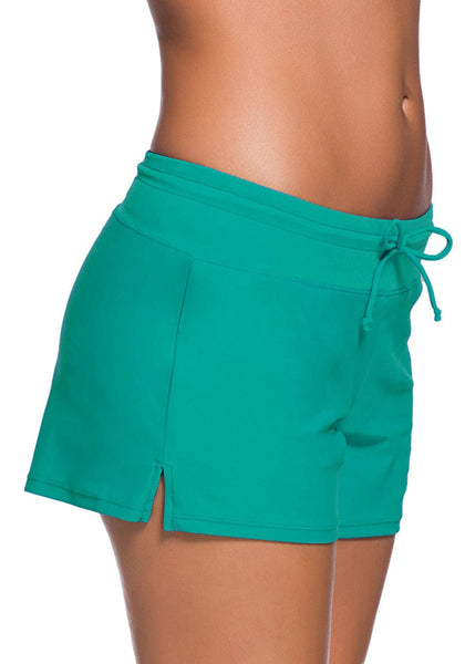 Right side shot of model in turquoise drawstring side-slit board shorts