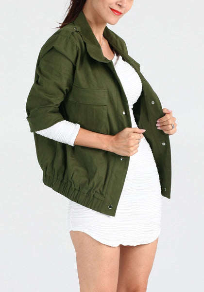 Right side view of girl in moss green button-down military jacket