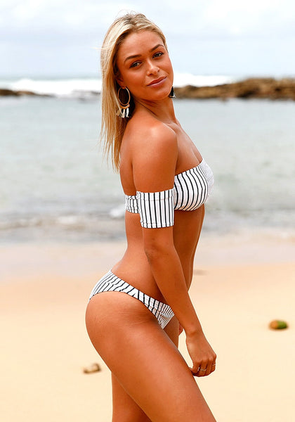 Right side view of model in black and white striped off-shoulder bikini set