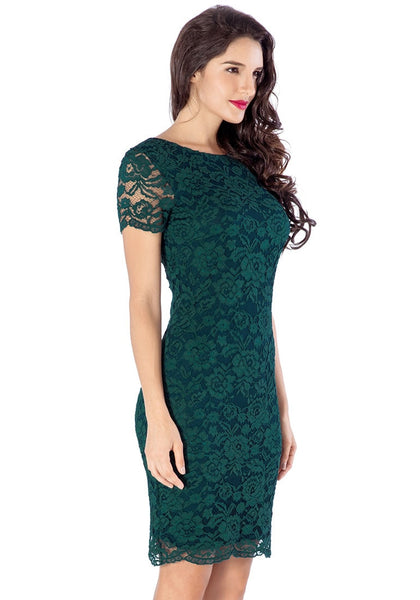 Right side view of model in green lace overlay shift dress