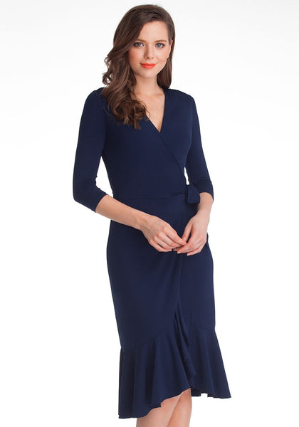 Slightly angled shot of woman wearing navy blue asymmetrical ruffled wrap dress
