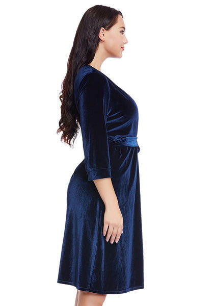 Right side view of model wearing plus size navy blue velvet wrap dress