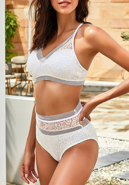 Sexy model poses wearing white fishnet-trim high waist lace bikini set