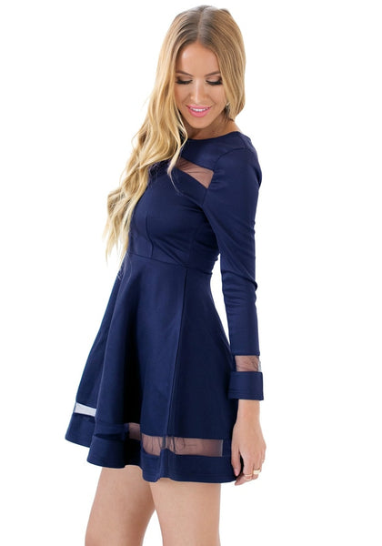 Side angled shot of model in navy mesh panel skater dress