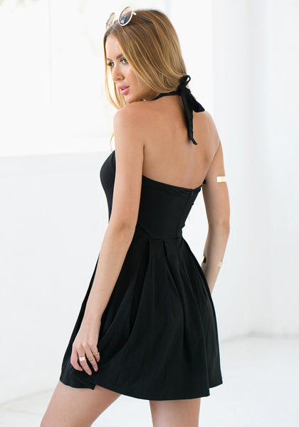 Side back of model in black halter skater dress