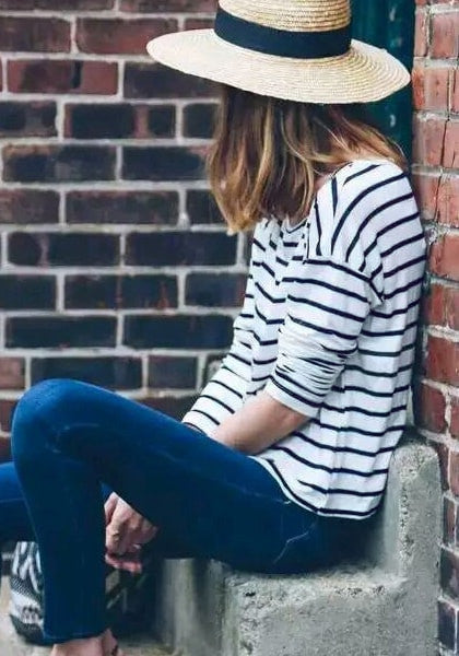 Side shot of model sitting down, wearing a black and white striped long-sleeves top and a hat