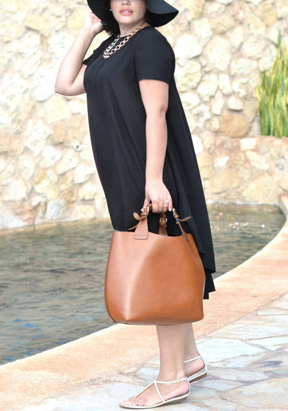 Side shot of woman in black hi-lo trapeze tunic and brown bag
