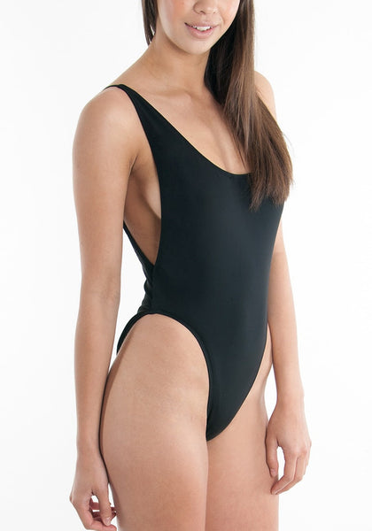 Side view of model in black classic low-back swimsuit