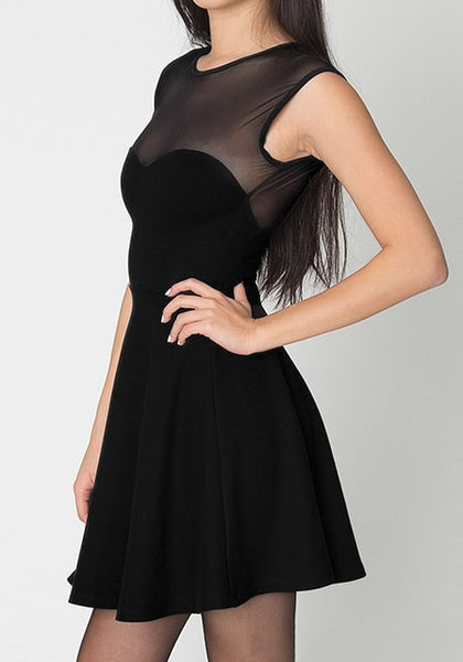 Side view of model in black illusion-neck sleeveless mini dress