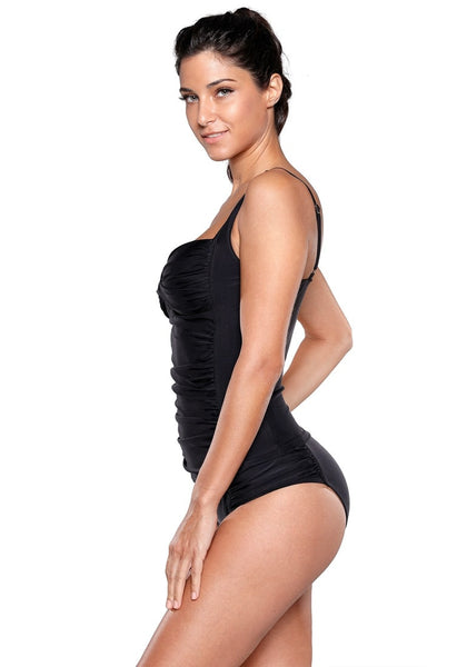Side view of model in black ruched tankini set