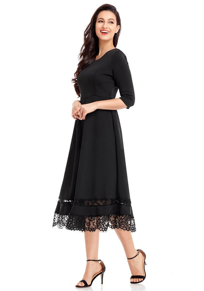Side view of model in black scallop hem lace panel skater dress