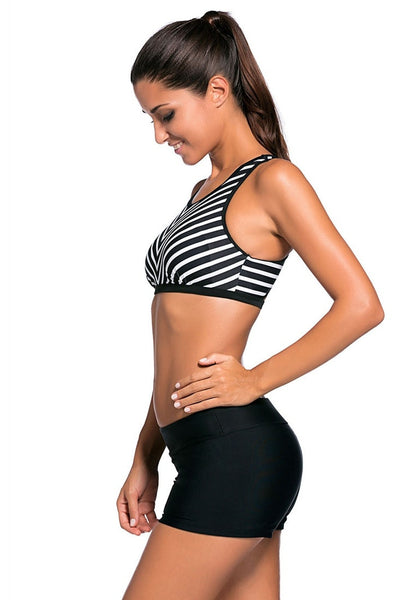 Side view of model in black striped sports bra two-piece set