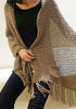 Side view of model in brown tassel knit shawl sitting down