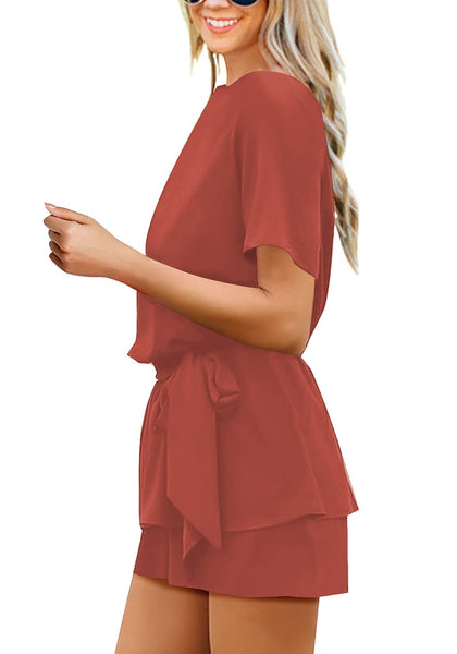 Side view of model in dark coral pink short sleeves keyhole-back belted romper