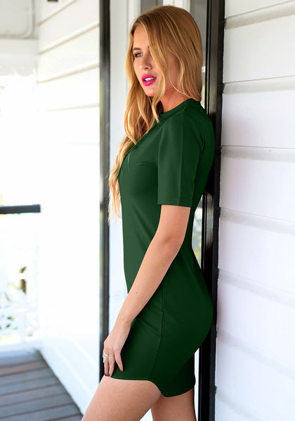 Front view of  model in dark green curved hem bodycon dress