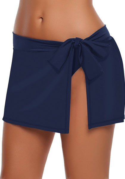 Side view of model in navy side slit bowknot swim skirt