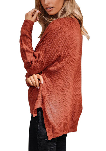 Side view of model in rust red ribbed knit textured side-slit sweater