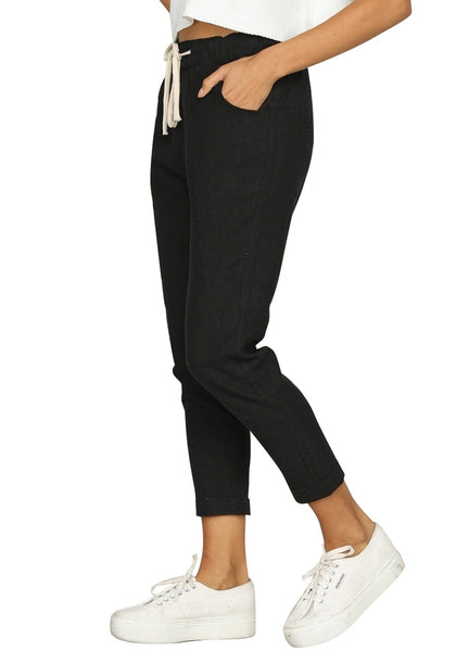 Side view of model wearing black drawstring-waist rolled-up cropped pants