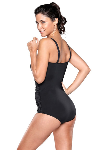 Side view of model wearing black ruched white-trim swimsuit