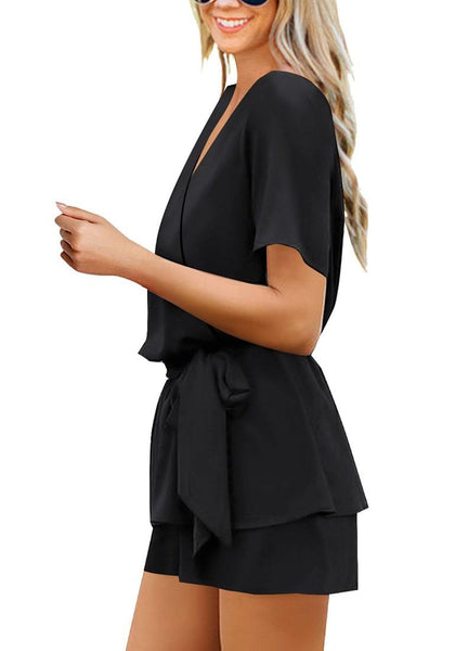 Side view of model wearing black short sleeves layer belted surplice romper