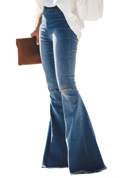 Side view of model wearing blue elastic-waist distressed denim bell bottom jeans