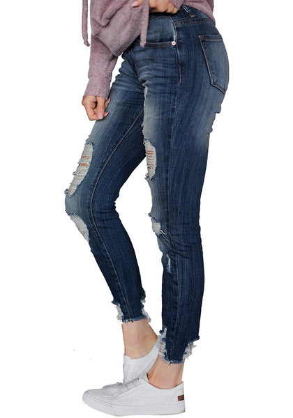 Side view of model wearing blue raw hem distressed cropped skinny jeans