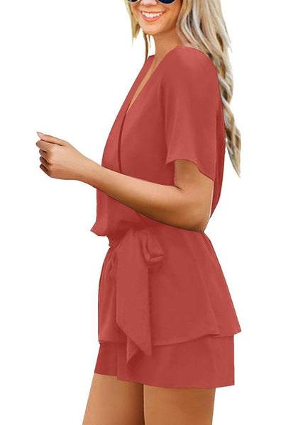 Side view of model wearing coral short sleeves layer belted surplice romper