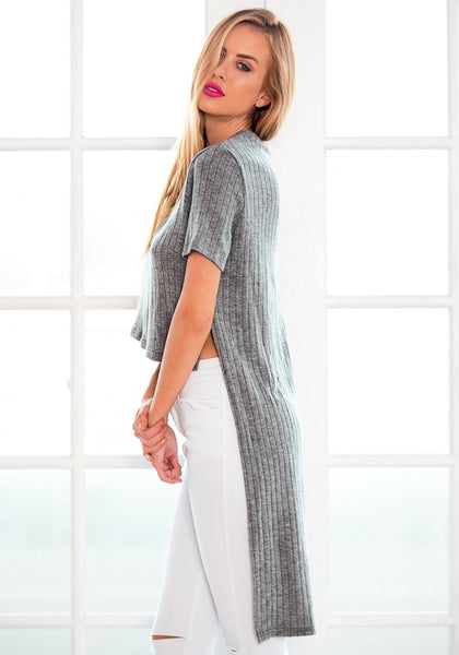 Side view of  model wearing grey high-low knit top