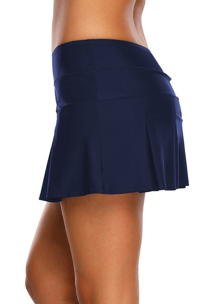 Side view of model wearing navy blue pleated mid-waist skirt