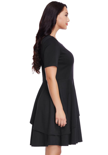 Side view of model wearing plus size black asymmetric layered skater dress