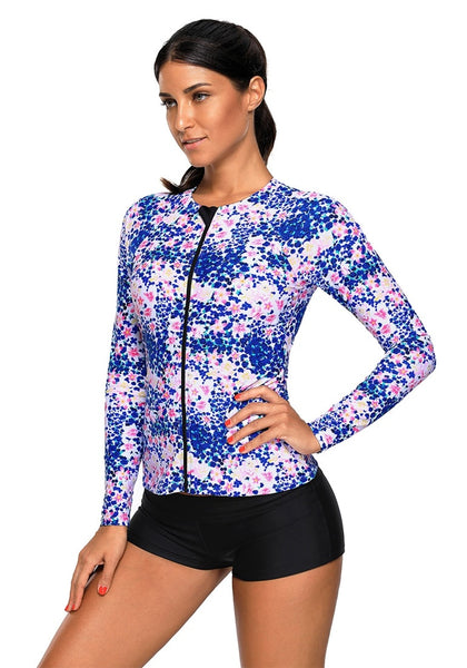 Side view of model wearing royal blue floral print zipper-front swim top