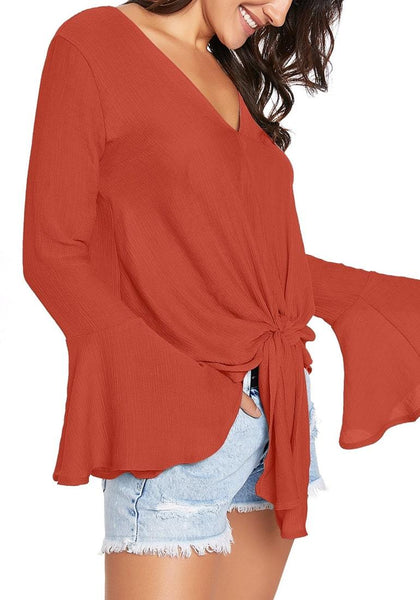 Side view of model wearing rust V-neck trumpet sleeves tie-front blouse