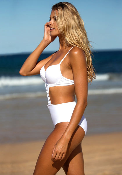 Side view of model wearing white crisscross-front monokini in the beach