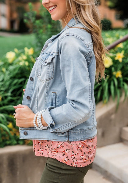 Side view of model wearing light blue button down women's denim jacket