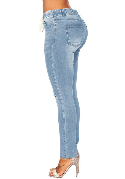 Side view of light blue drawstring-waist washout ripped skinny jeans