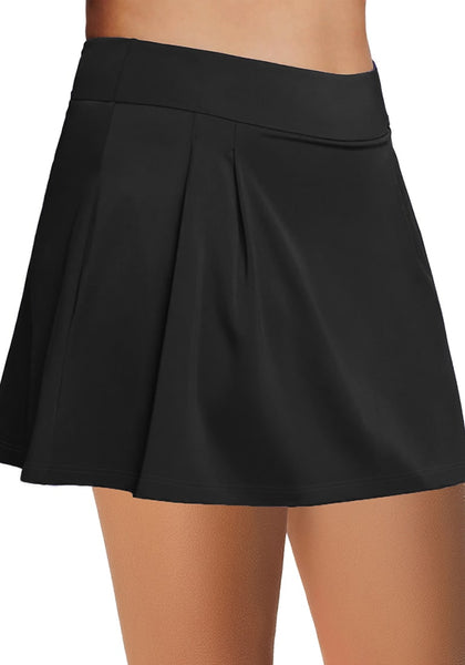 Side view of model wearing black pleated side mid-waist swim skirt